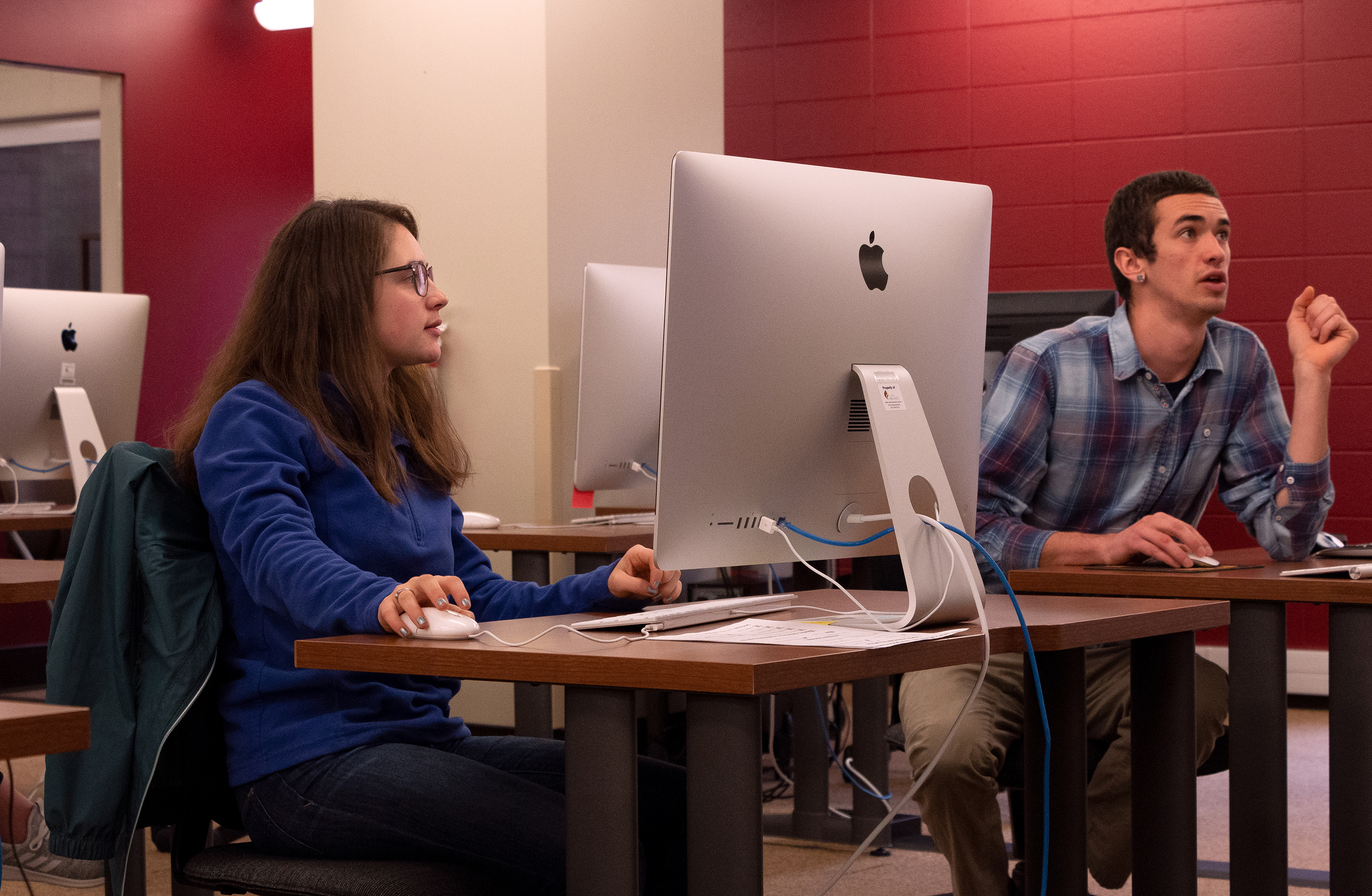 Two students working in a Mac computer lab.