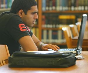 Student using laptop in the reference room