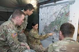 Military personnel studying a map