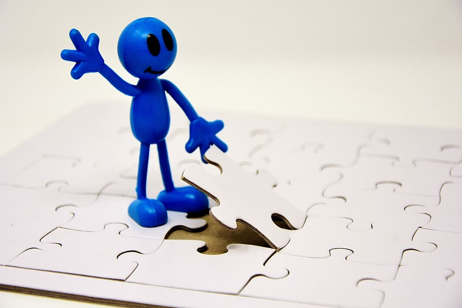 blue figure putting in last white puzzle piece