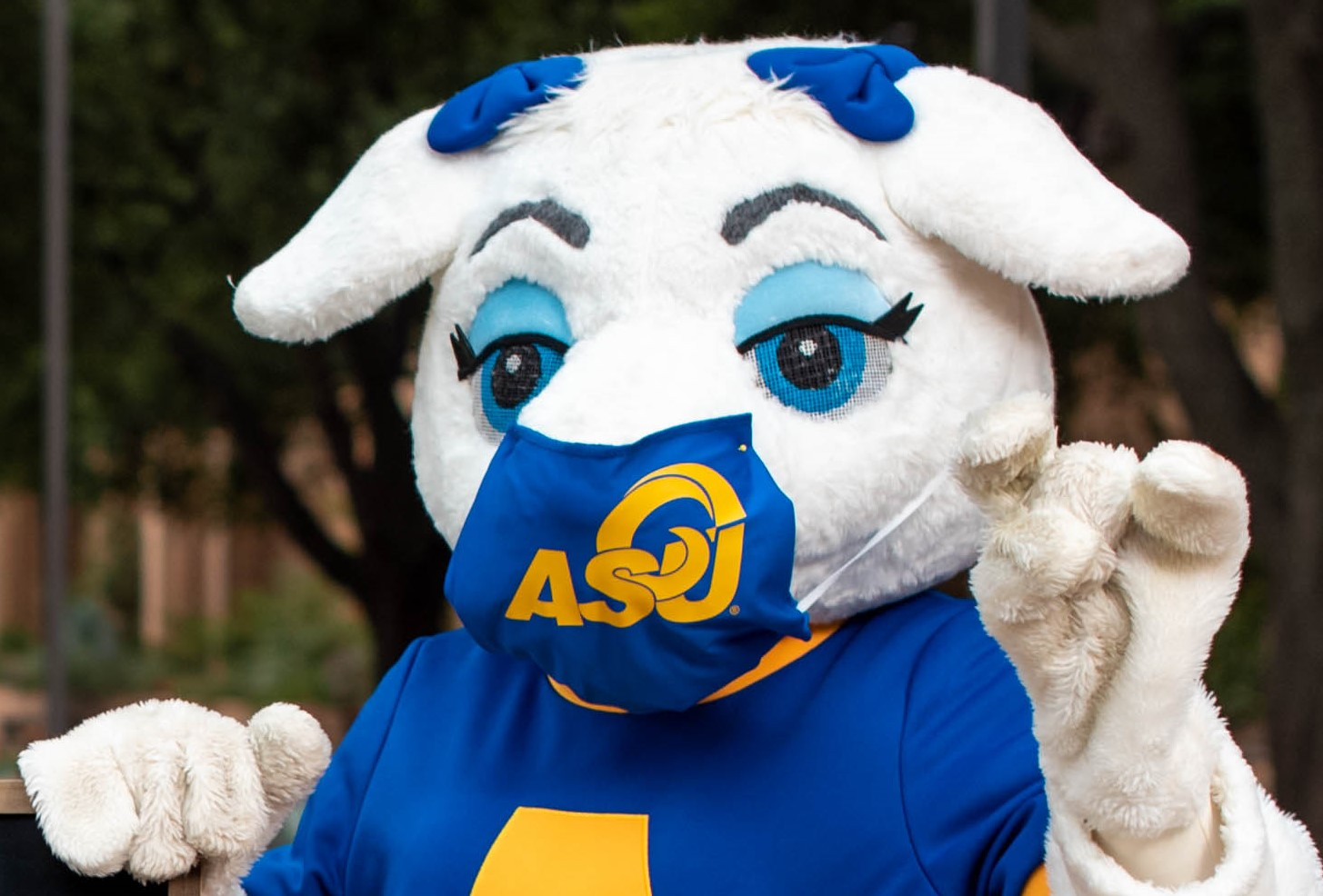 Bella, the lady Ram mascot, wearing face protection and giving the ASU sign.