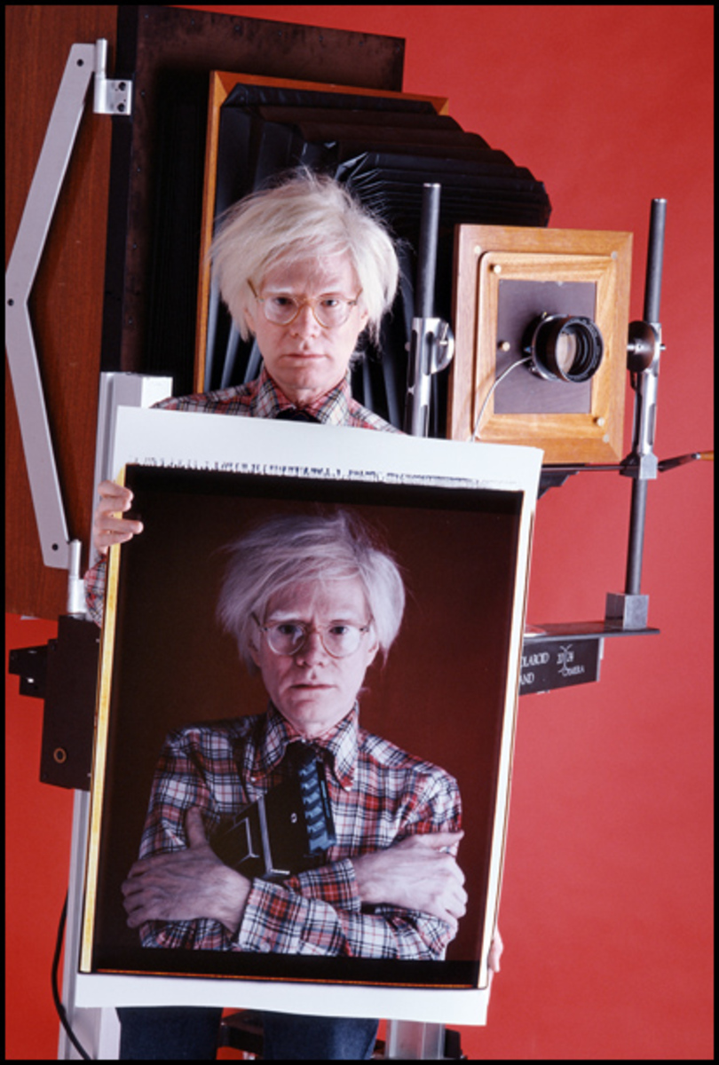 "Andy Warhol posing with the 20"" x 24"" Polaroid camera and the large self portrait it produced."