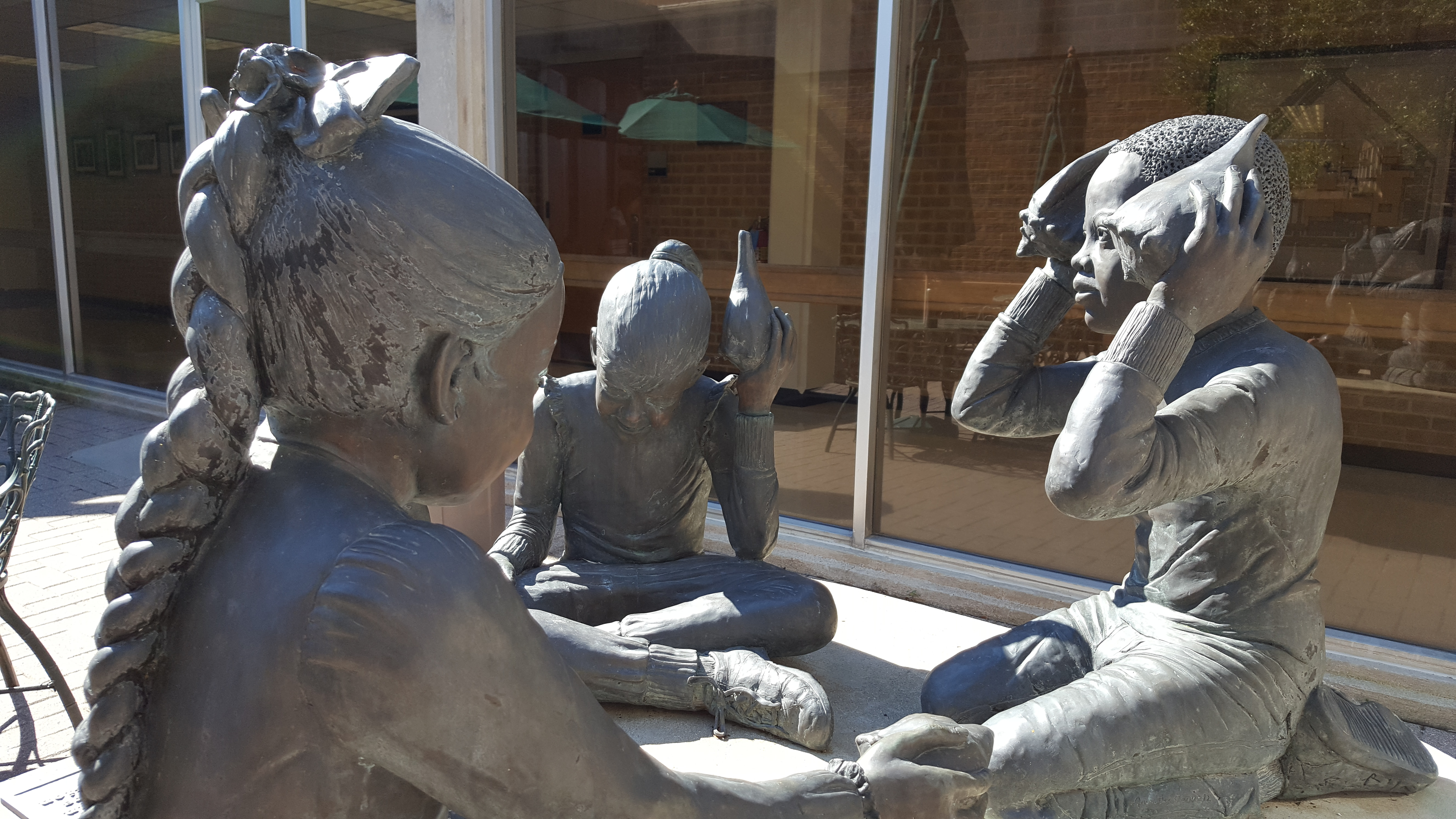 Photograph of the sculpture found in the Calier Center Atrium. Three children play with seashells against their ears and mouths.
