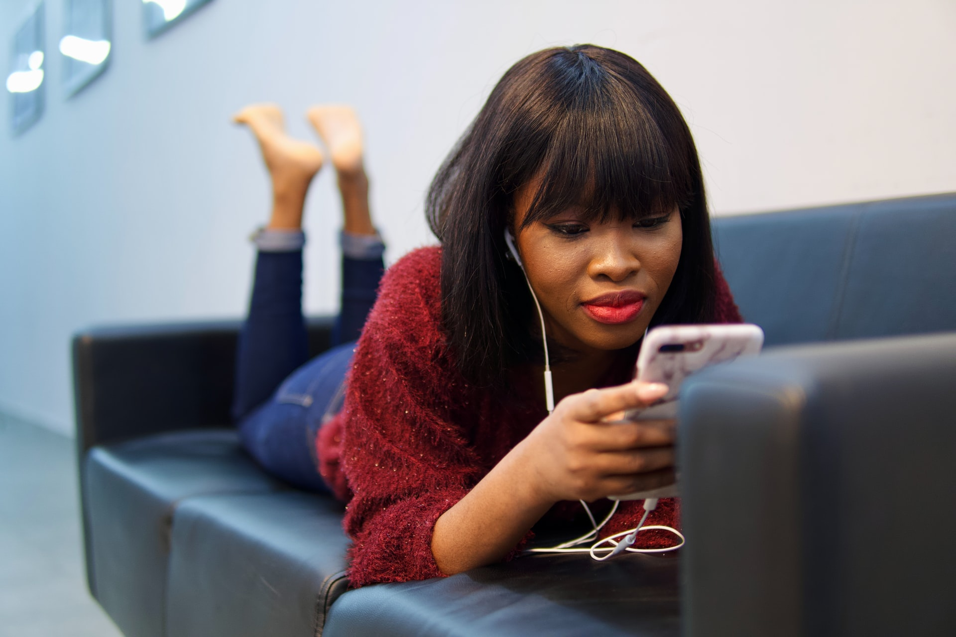 Woman lounging on a couch with her phone and earbuds.