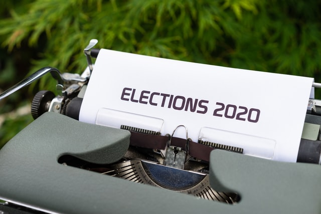 "image of a type writing with a paper loaded into it reading ""elections 2020"""