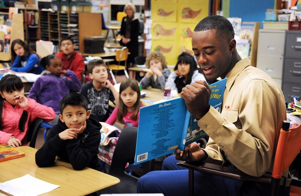 Man reading a book to children.