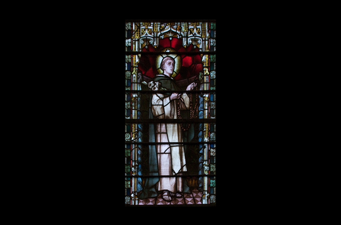 Stained glass window depicting St Dominic holding a rosary