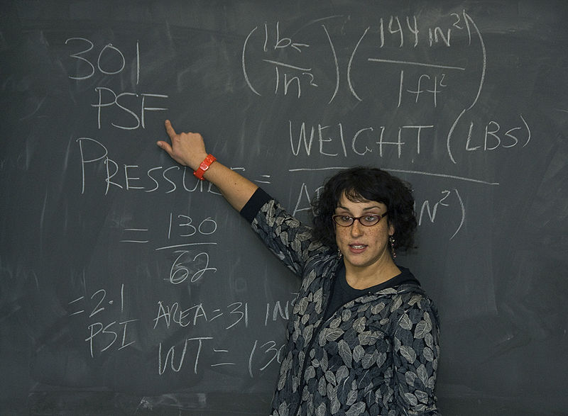 Female engineer pointing at a math equation on the chalkboard.