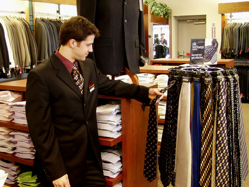 A man selling ties in a store