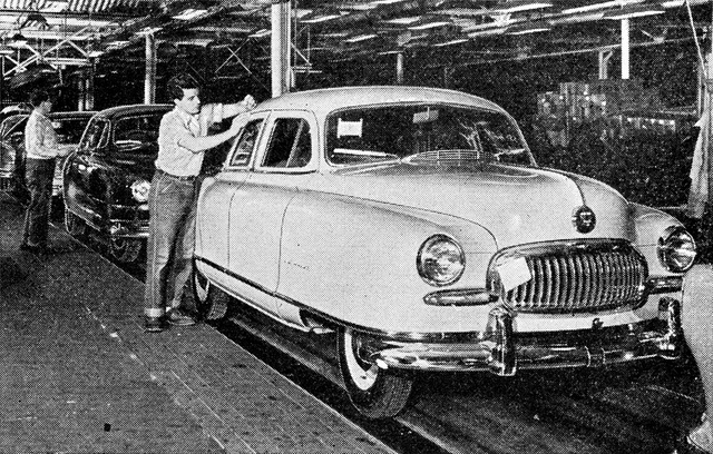 Two men working on an automobile assembly line