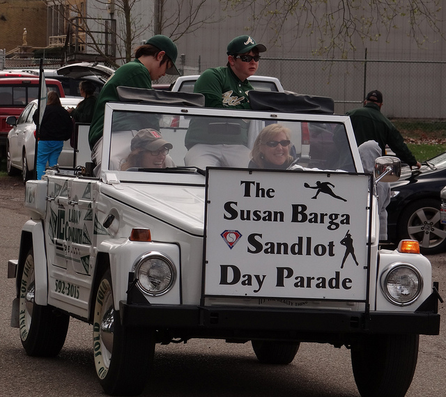 a picture of two baseball players riding in the back of a convertible during a parade