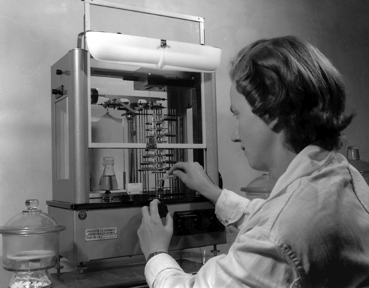 Black and white photograph of female chemist in analytical chemistry lab.