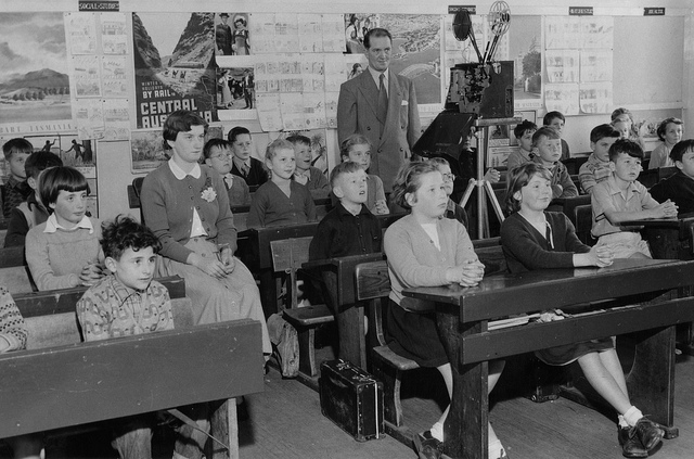 Black and white picture of classroom with a teacher showing a film to his students.