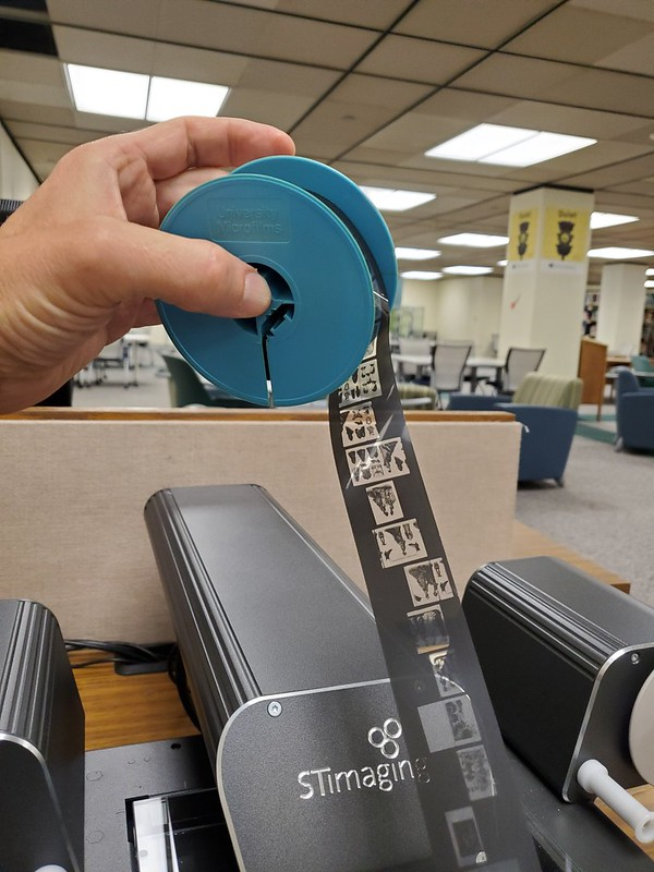 image of hand holding a blue plastic spool with microfilm being pulled out