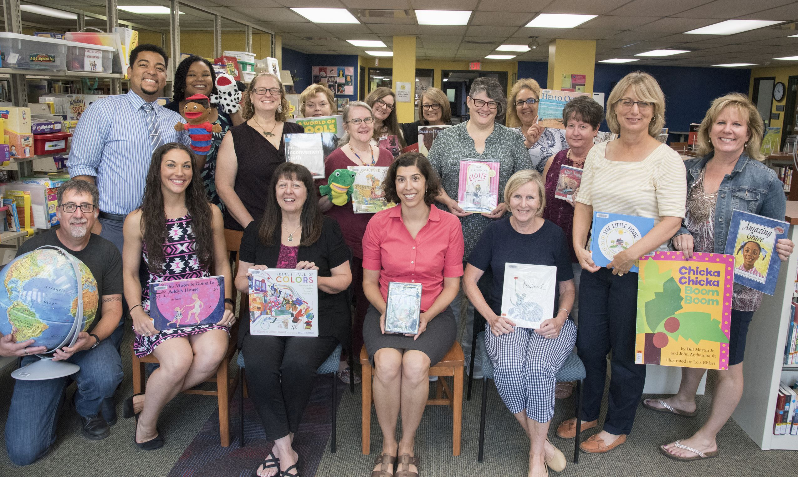 McQuade Library Staff August 2019 seated and standing holding books, toys, and other items available in the Educational Resource Collection