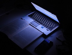 lighted half open laptop, book, and phone