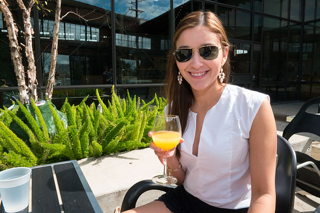 woman sitting with mimosa or bellini, we can't really tell