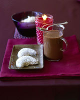Hot chocolate with biscuits and a candle