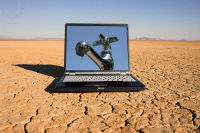 Laptop displays image of dripping faucet, set in a desert