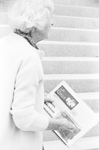Woman holding La Raza newspaper