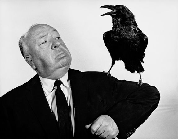 HItchcock with crow perched on his arm.