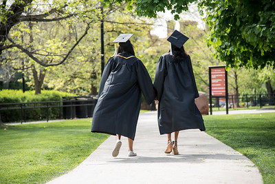 Two CU students in graduation robes walk near the Norlin Quad
