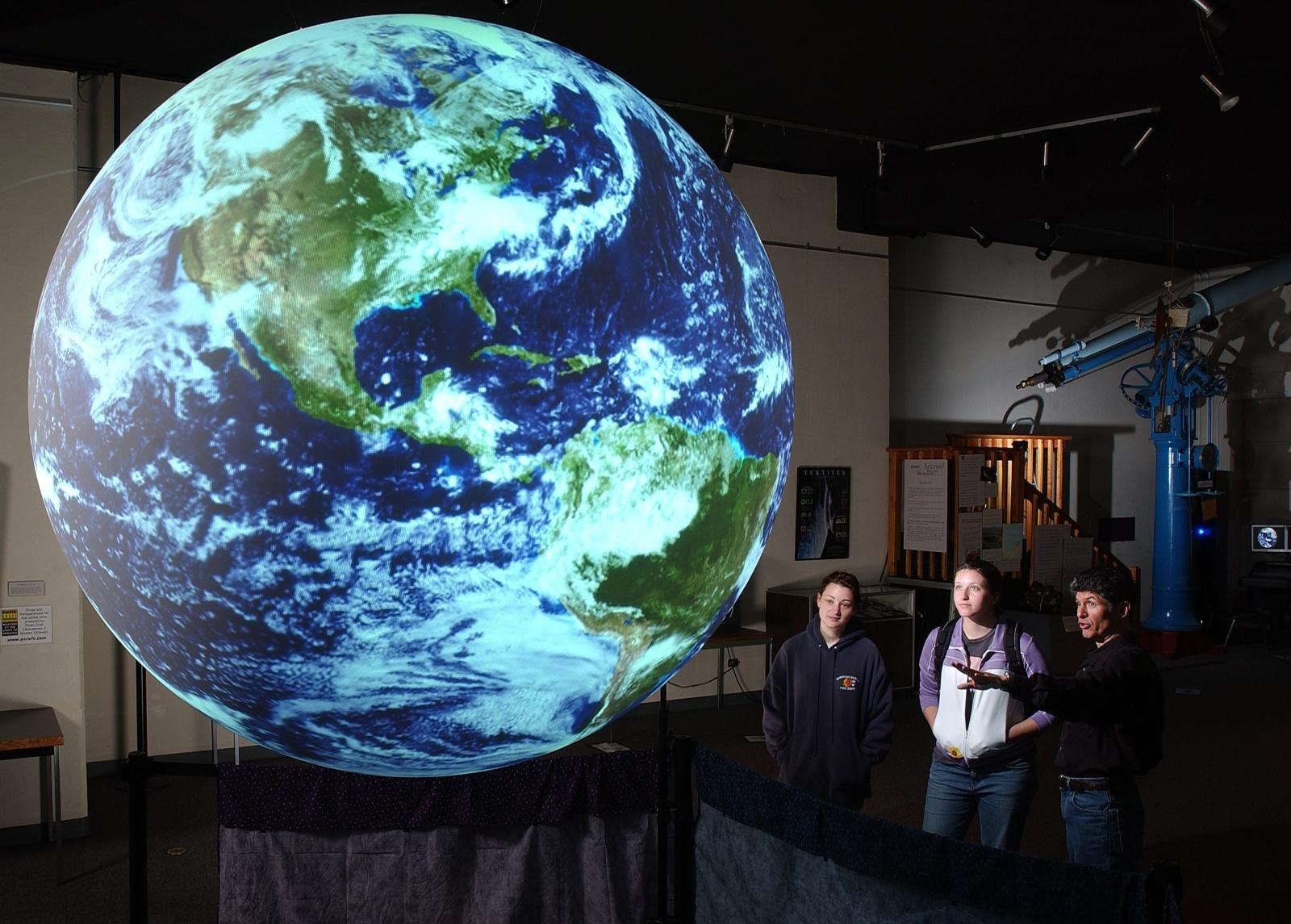 Three students gaze at a giant sphere of the earth at the Planetarium