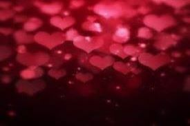 multiple pink blurring hearts falling aganist a black background
