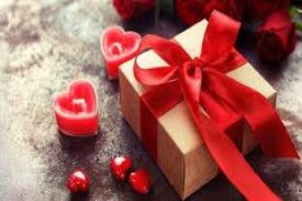 small gold box wrapped with a red ribbon sitting on a dinner table; small red hearts around it