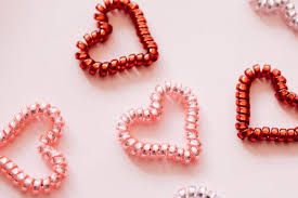red and pink beads arranged in small heart-like shapes