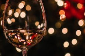 one wine glass with mini lights in the background