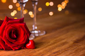 open red rose laying next to two wine glasses with a tiny red candy heart in the front