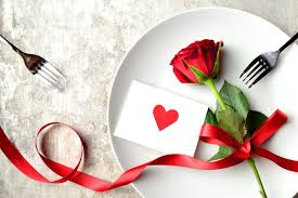 one rose laying across a white dinner plate