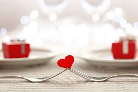 two silver forks holding up a small red heart