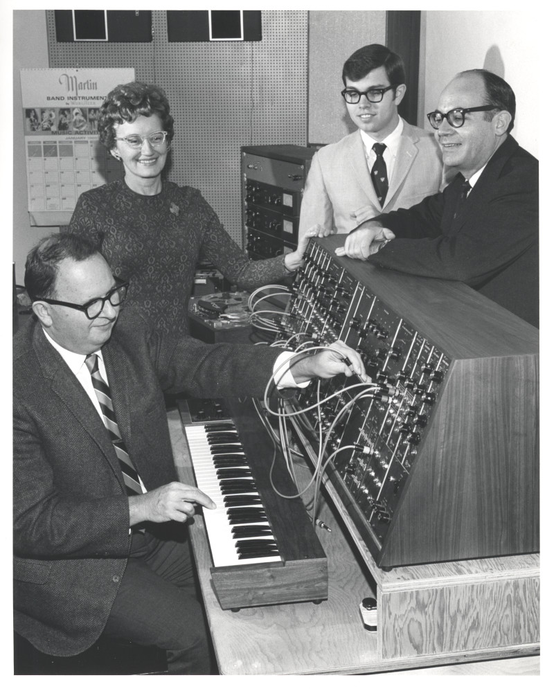 Four individuals experimenting with early electronic music set-up