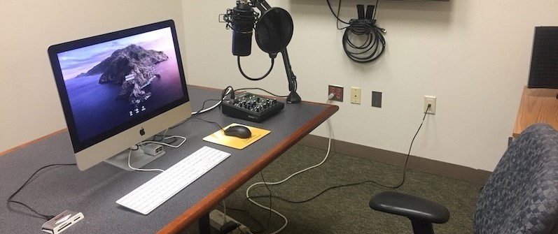 This is the recording booth set up with iMac, small soundboard, microphone, pop filter, and headphones.