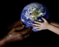 Earth held in hand of black adult and white child