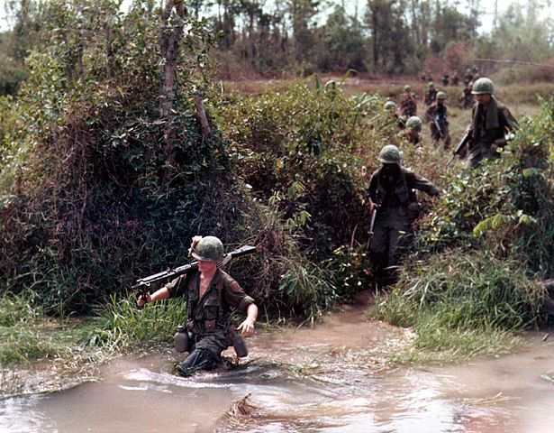 soldiers wading through a river in vietnam
