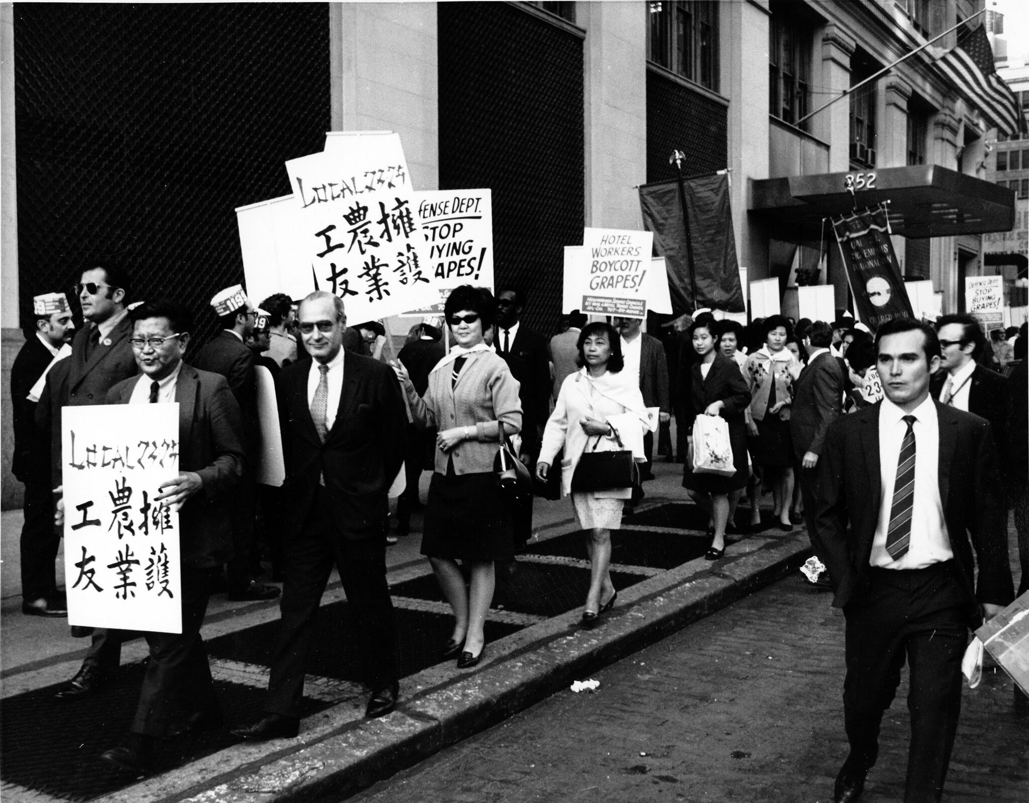 Members of ILGWU Local 2329, ILGWU Local 23-25, and SEIU Local 1199 picket for a boycott on grapes. Several Asian Americans are present with placards in Chinese.
