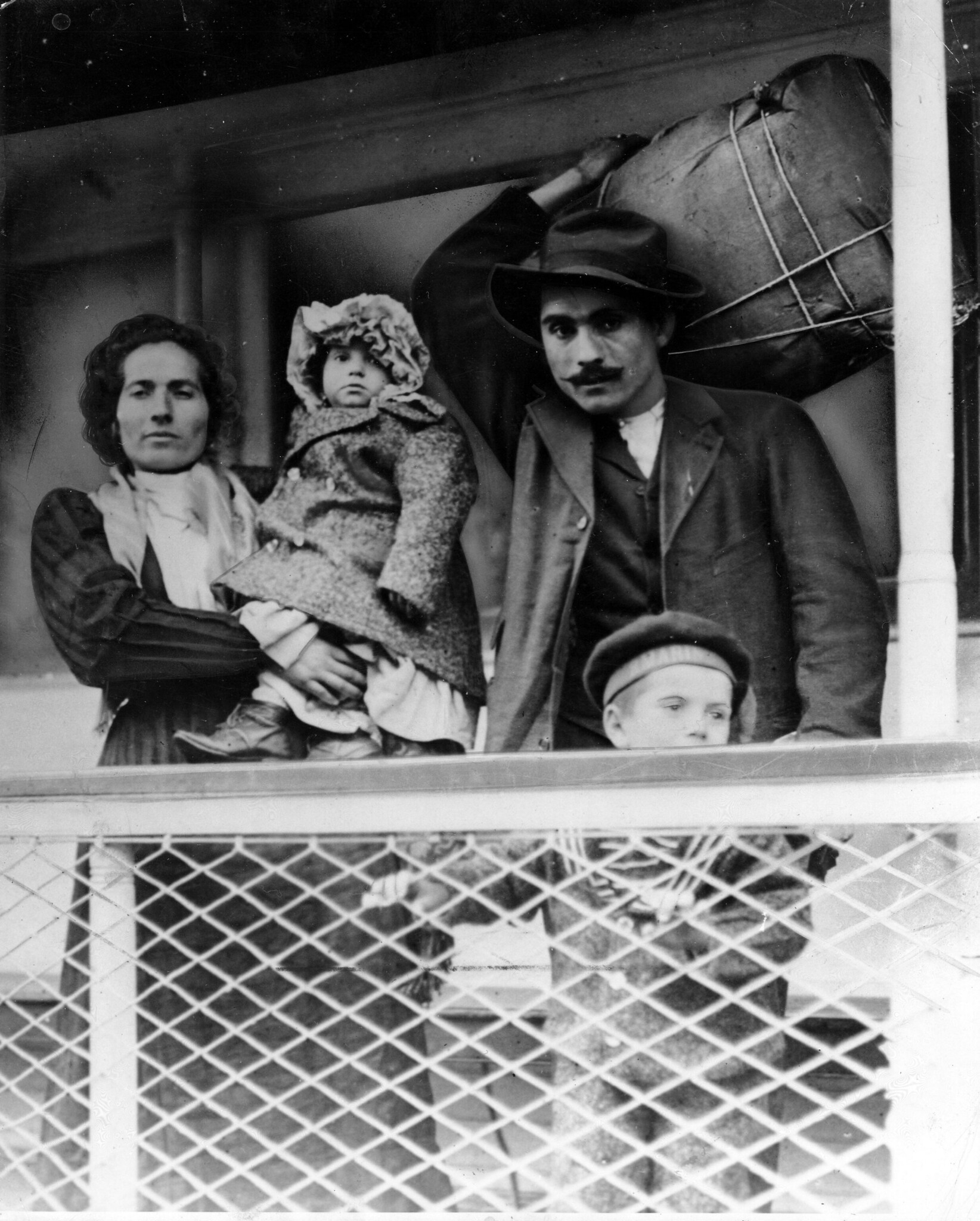Immigrant family on a ship. Man holds their bundle