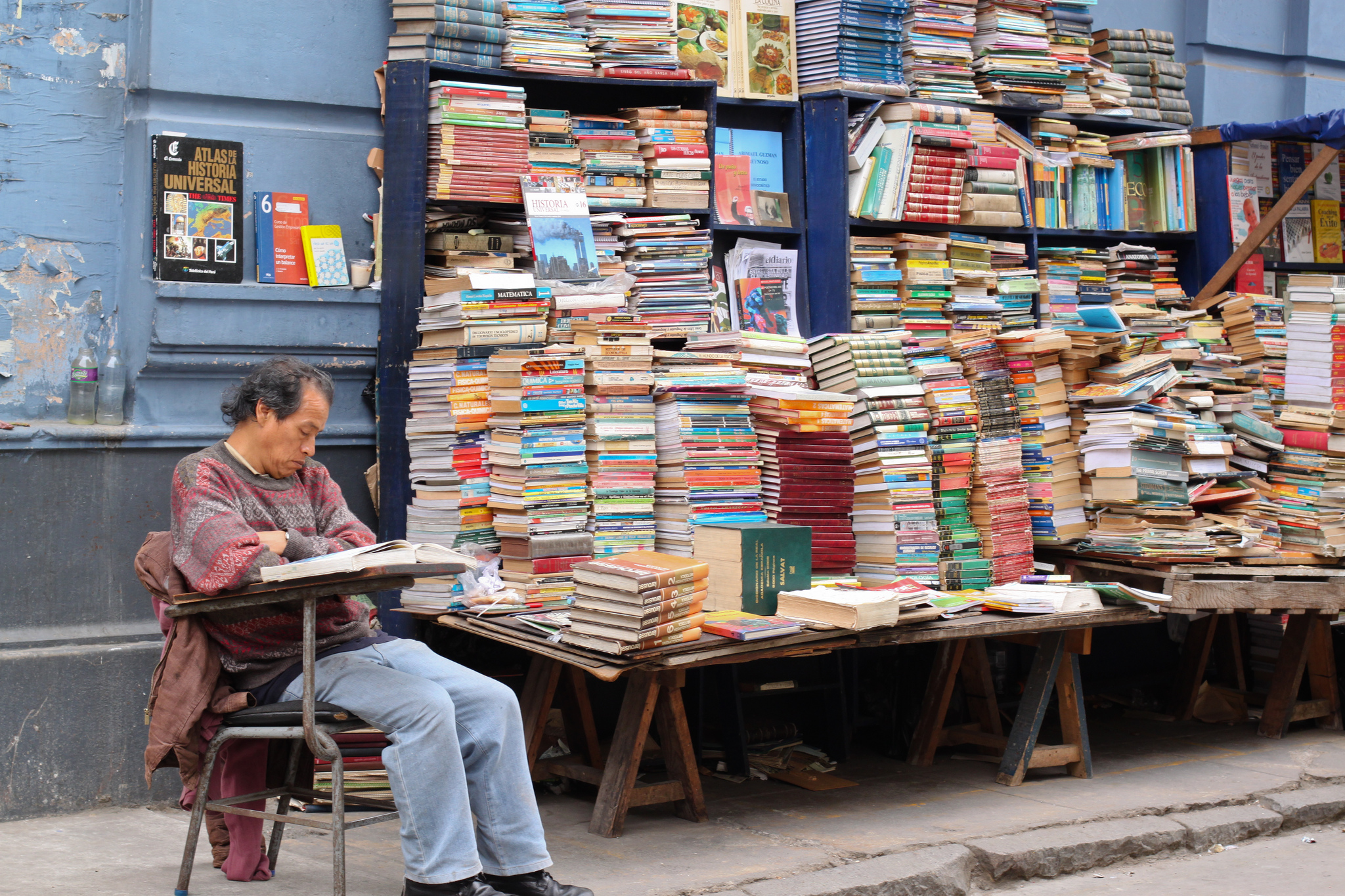 Man Asleep at a desk in front of piles of books on the street