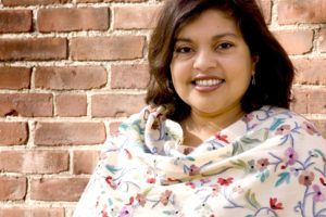 author Mitali Perkins in front of a brick wall
