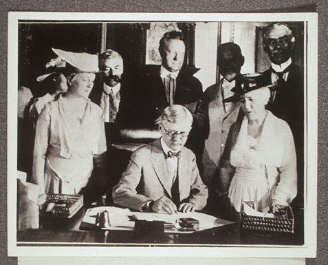 Vice President Marshall, signs the 19th Amendment with a group of men and women. June 5, 1919.