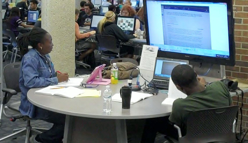 two students are facing the large TV monitor at a collaborative study table