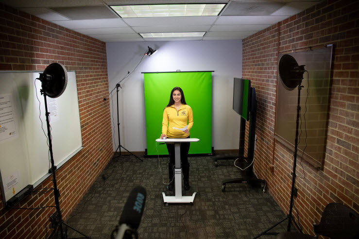 college-age female is standing in middle of room in front of green screen and behind microphone