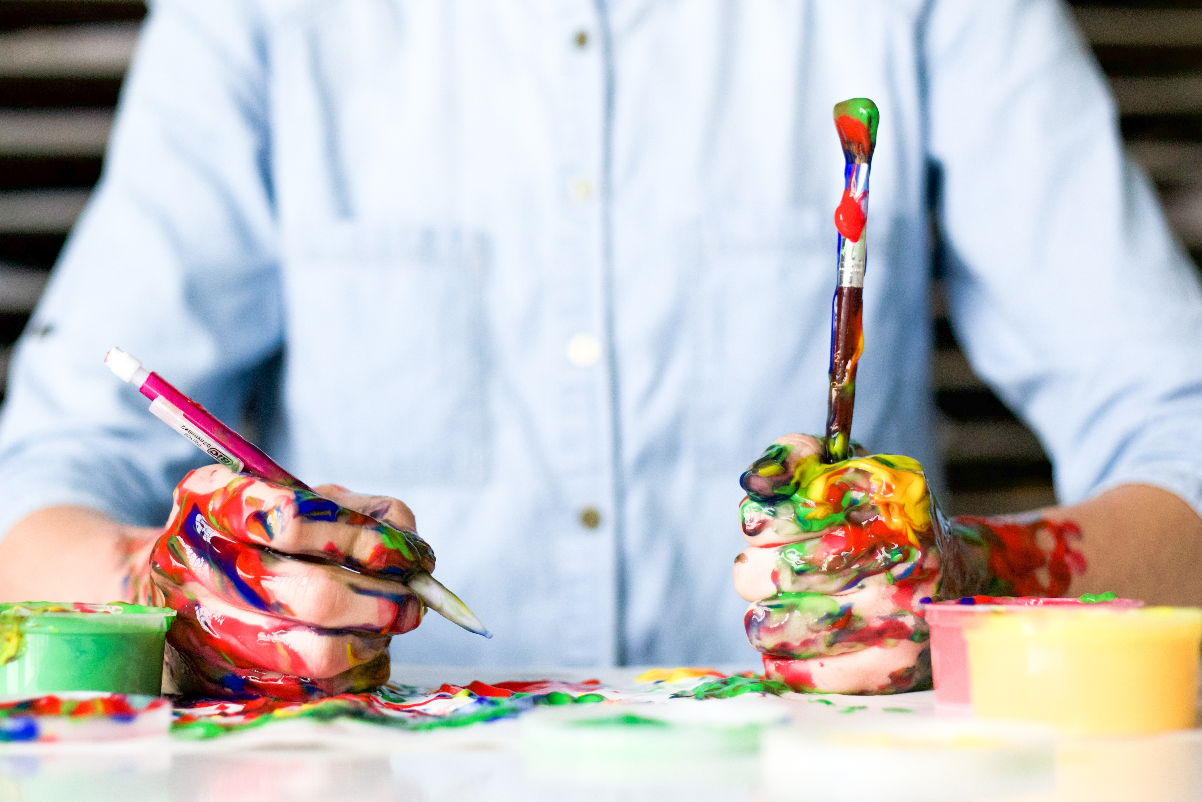 man's hands covered in paint and holding a pen and paintbrush