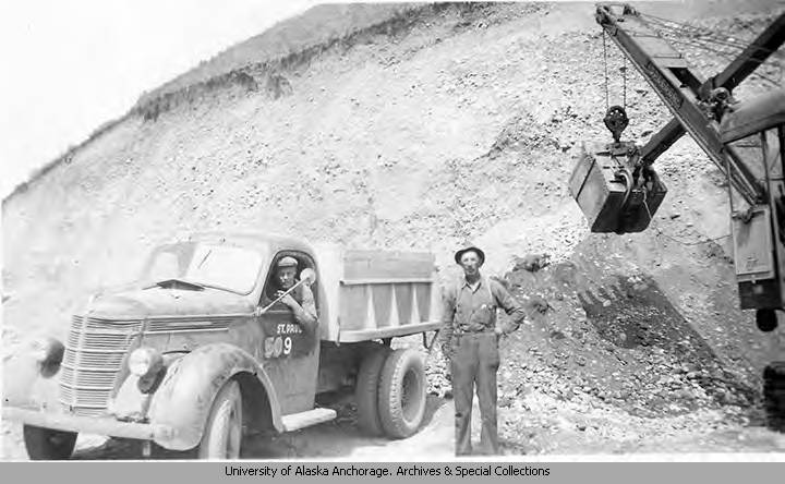 A construction worker poses next to a cable excavator and a dump truck with driver