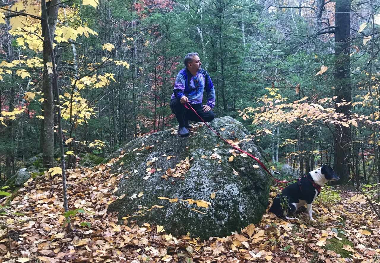 Photo of Richard Cohen seated on a large rock in the woods with his dog Willow below