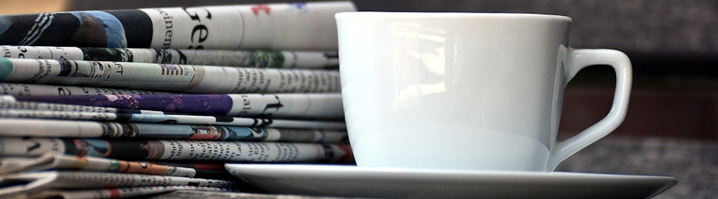 Folded newspapers, stacked beside a coffee cup