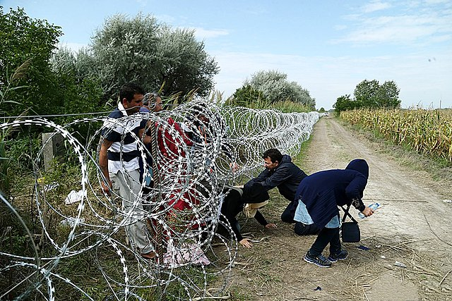 migrant people crossing barbed wire fence